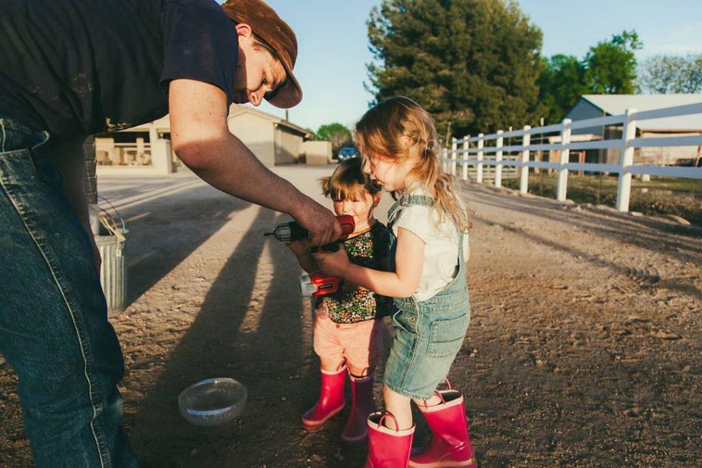 dad hands drill to children